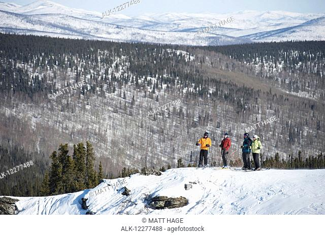 Friends take in the view during a day of downhill skiing at Mt. Aurora Skiland near Cleary Summit north of Fairbanks, Alaska