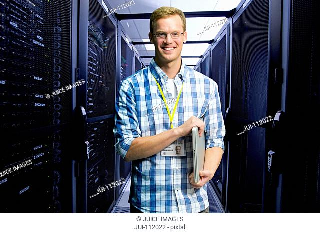 Technician with laptop smiling at camera and checking in data centre server hall