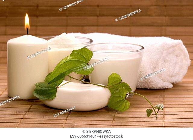 white bath items. soap, towel, milk, candle. spa