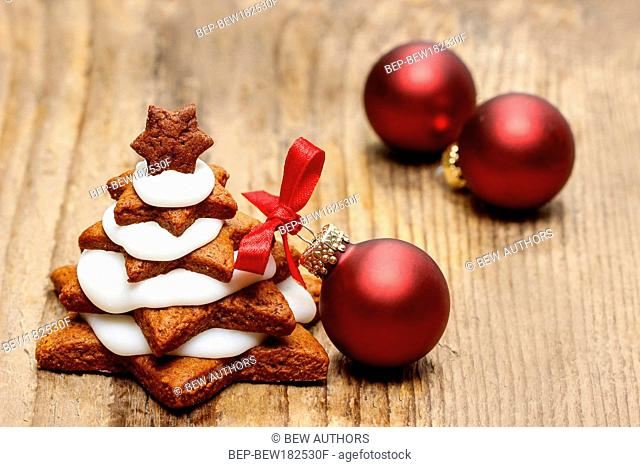 Gingerbread christmas tree and red christmas balls on wooden table. Beautiful xmas setting