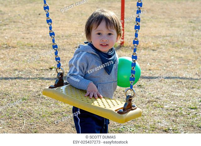 A 2 year old boy holding a ball and standing by the swings at a playground
