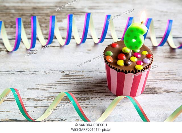 Birthday muffin with chocolate buttons and lighted candle