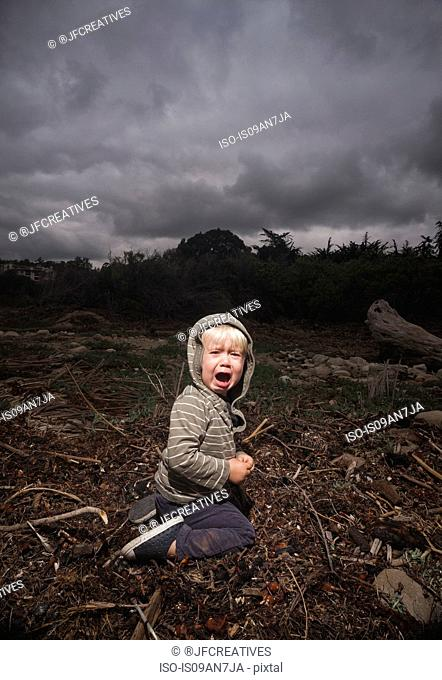 Young boy kneeling on ground crying against stormy sky
