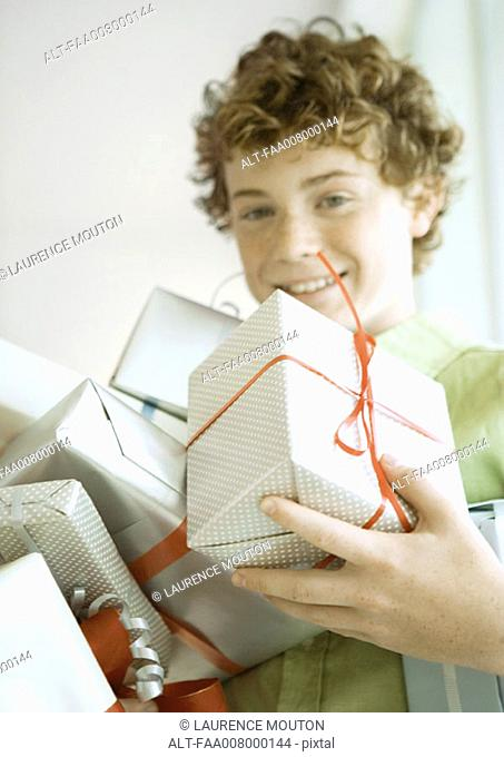 Boy holding armful of presents