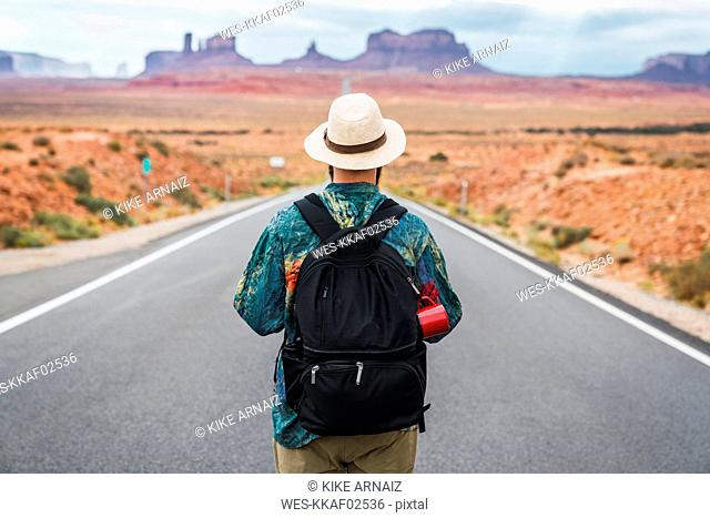 USA, Utah, Man with backpack standing on road to Monument Valley
