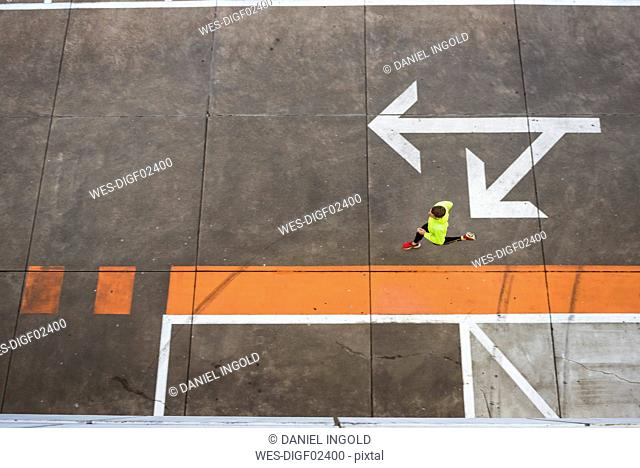 Young man running on parking level