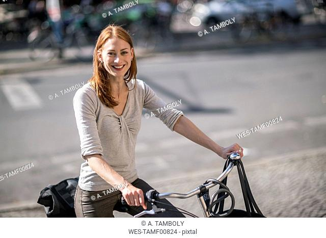 Portrait of redheaded woman with bicycle