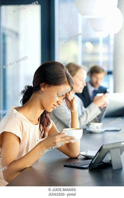 Frustrated businesswoman with digital tablet in coffee shop
