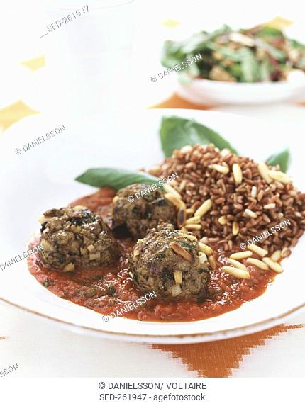 Meatballs with tomato sauce, pine nuts and red rice