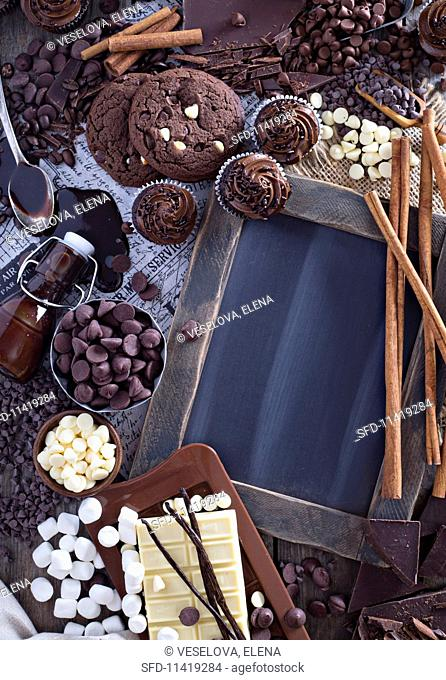 An arrangement of chocolate cookies, cupcakes, chocolate chips, syrup, marshmallow and cinnamon sticks