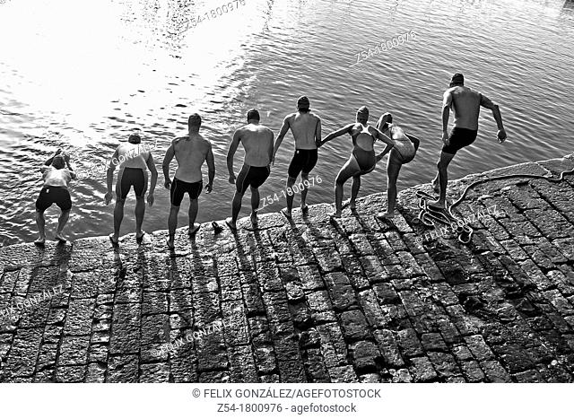 Competitors jumping into water at Gijón Marina, in a swimming race, Asturias, Spain
