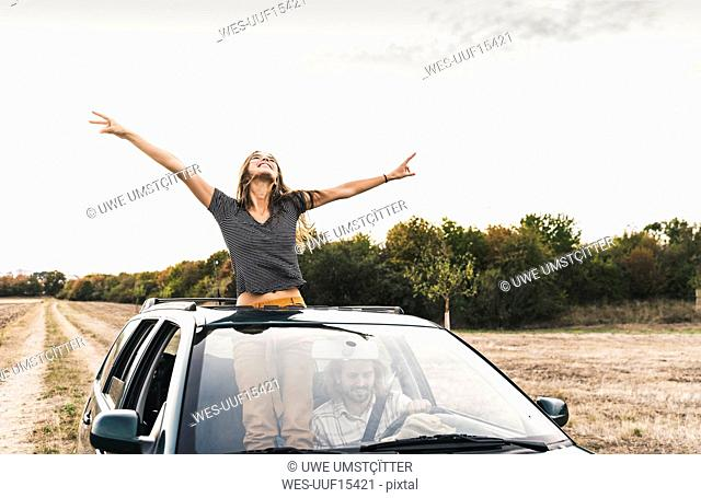 Carefree young woman looking out of sunroof of a car