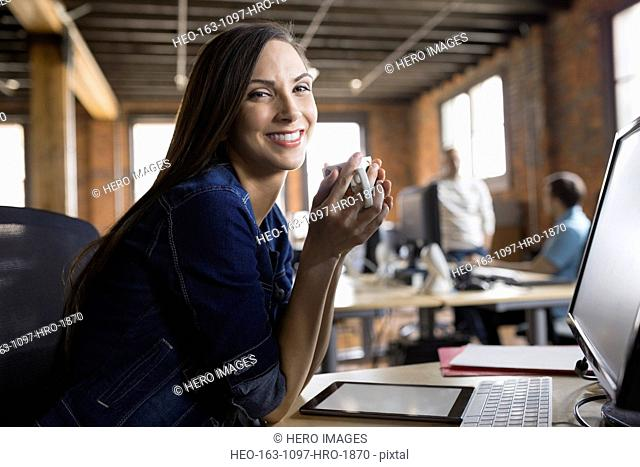 Portrait of smiling businesswoman drinking coffee in office