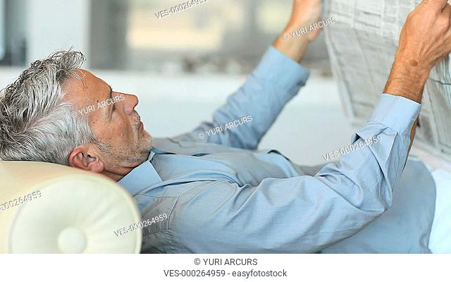 A mature man reading the newspaper while relaxing at home
