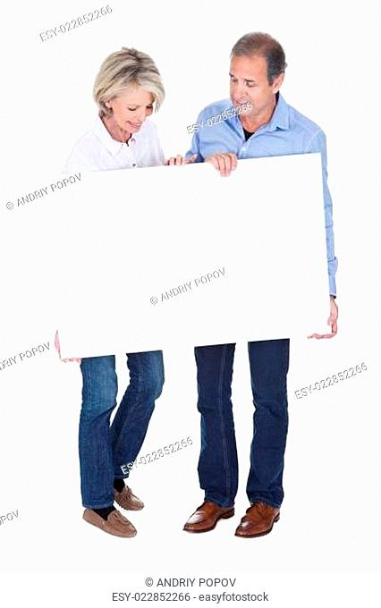 Portrait Of Mature Couple Holding Placard