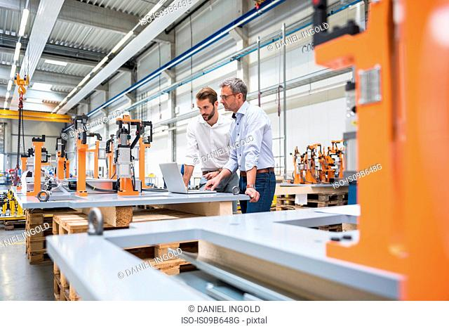 Two engineers with laptop looking at product in engineering factory