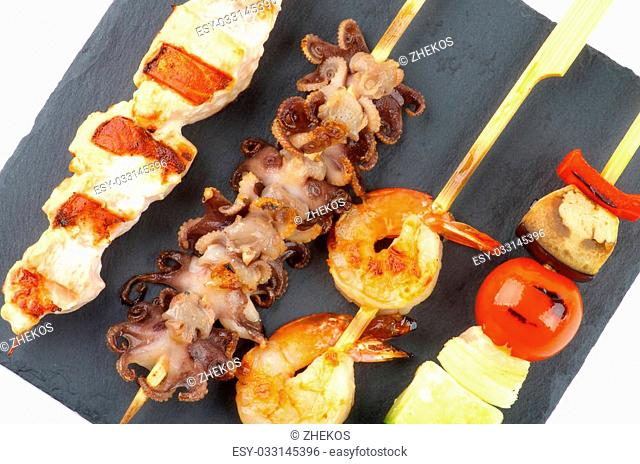 Grilled Salmon, Octopuses, Shrimps and Vegetables on Wooden Stick closeup Black Stone Plate. Top View