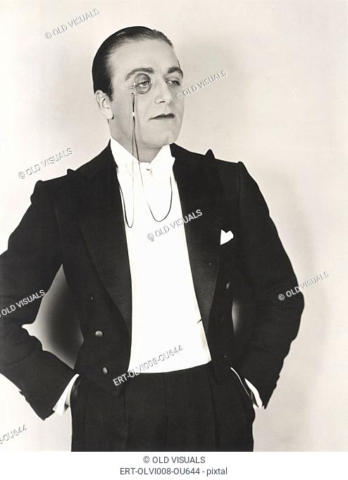Man wearing monocle and tuxedo with hands in pockets