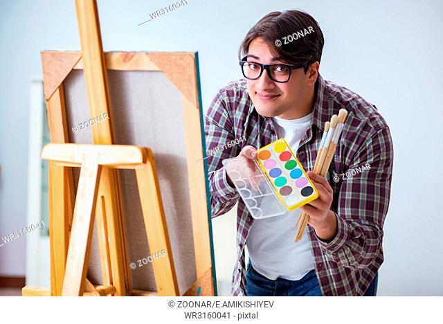 Young male artist drawing pictures in bright studio