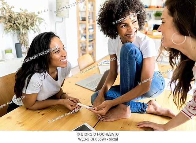 Three happy women talking at table at home