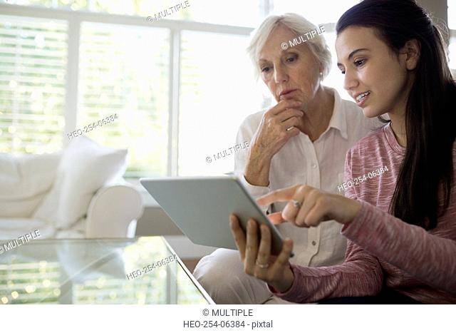 Grandmother and granddaughter using digital tablet living room