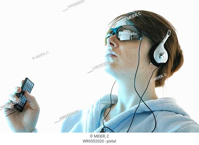portrait of a young woman wearing glasses and headset and holding the remote control in her hand -Brainlight - brainlight - brain light