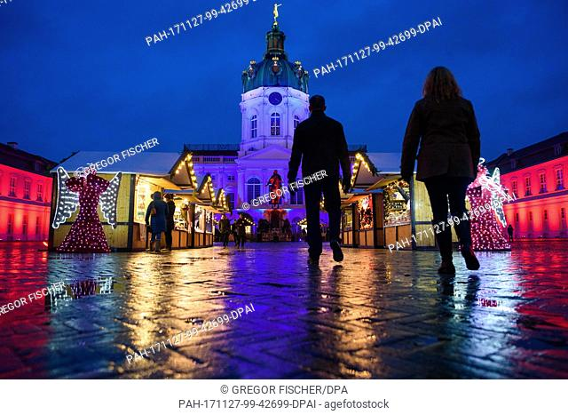 Visitors walk the grounds of the Christmas market in the rain in front of Charlottenburg Palace, which is illuminated in various colours, in Berlin, Germany