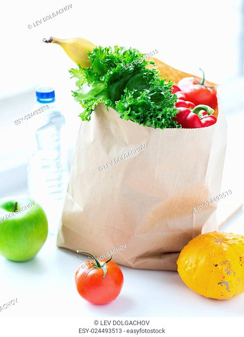 cooking, diet, vegetarian food and healthy eating concept - close up of paper bag with fresh ripe juicy fruits and vegetables and water bottle on kitchen table...