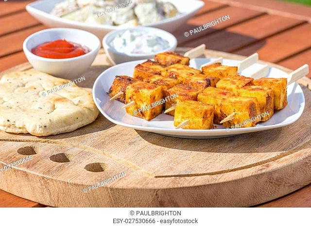 Paneer Tikka Kebab - Tandoori Indian cheese skewers with naan bread, chili sauce, and cucumber and yoghurt raita. Eating outdoors!