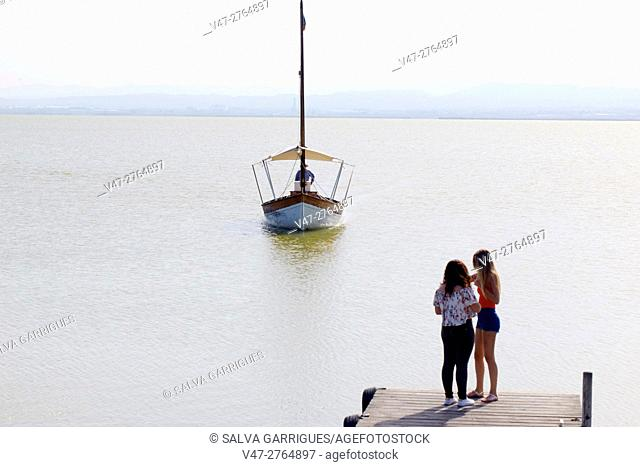 Two girls waiting for the boat at the pier of Lake Albufera of Valencia, Spain, Europe