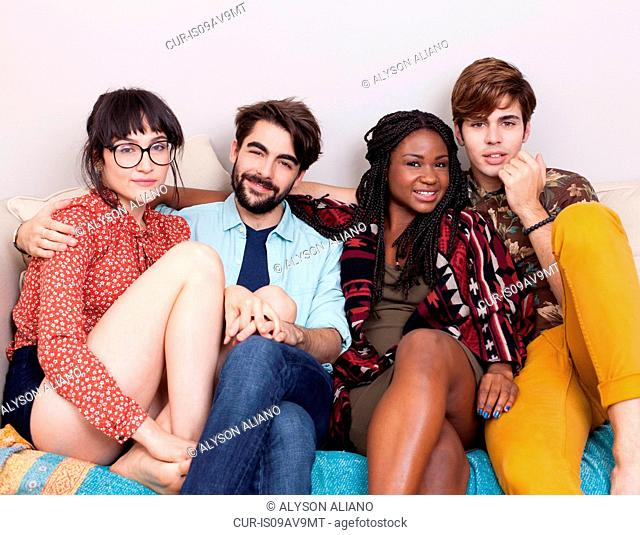 Portrait of four young adult hipsters sitting on sofa