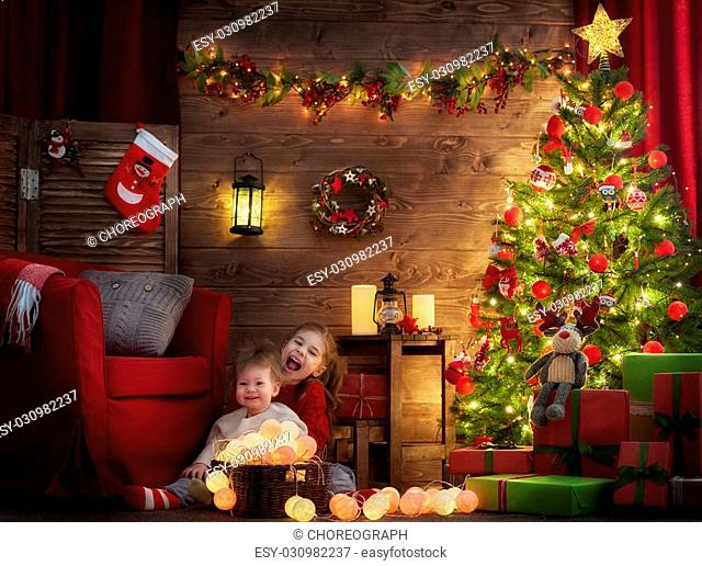 Merry Christmas and Happy Holiday! Two cute little children girls decorate the Christmas tree