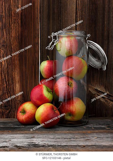 Fresh apples inside and next to a glass storage jar