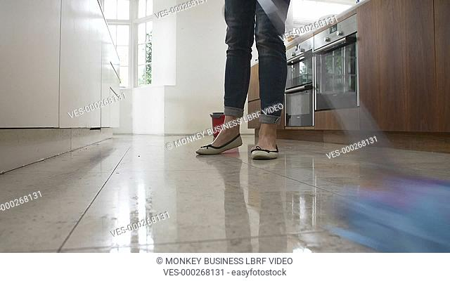 Speeded up time lapse sequence of woman cleaning kitchen floor with mop and bucket. Shot on Sony FS700 in PAL format at a frame rate of 25fps