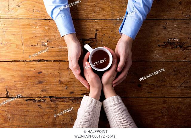Hands of a young couple holding mug of tea