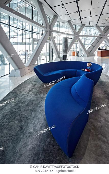 A 4 year old caucasian boy relaxes on a huge blue sofa in the reception lobby of the Hyatt Capital Gate 5 star hotel, designed by the architects RMJM Dubai...