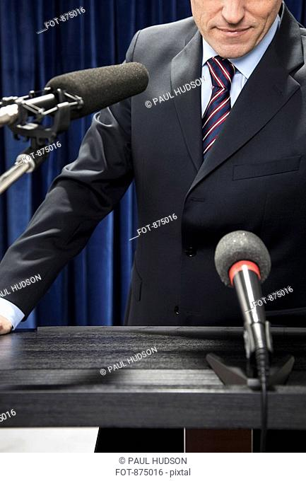 Detail of a man standing at a lectern