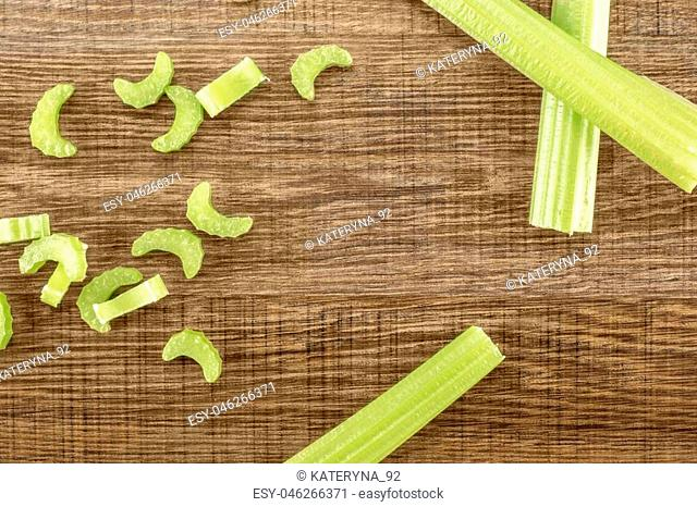 Three green celery sticks with fresh chopped pieces isolated on wooden background