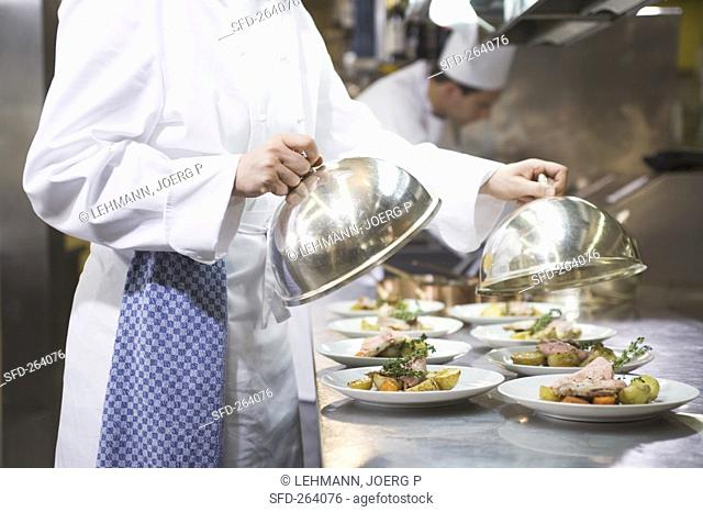 Female chef covering main courses with domed covers