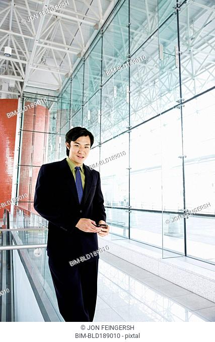 Asian businessman text messaging in airport