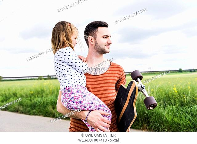 Father with skateboard holding daughter