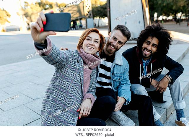 Three happy friends sitting outdoors taking a selfie