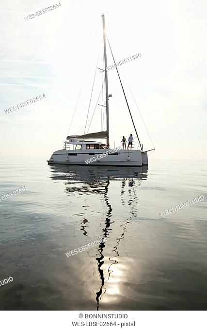 Couple setting off for a sailing trip on a catamaran