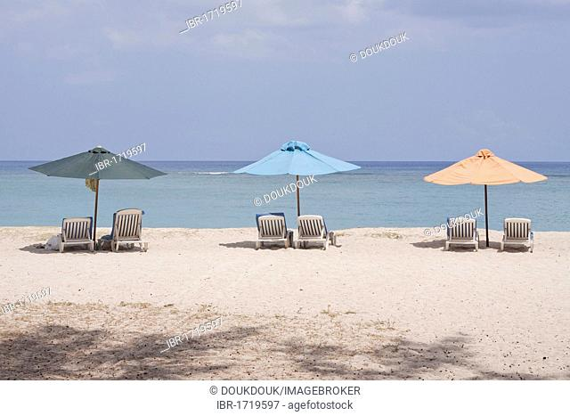 Sunloungers and beach umbrellas on the public beach of Flic en Flac, Mauritius, Africa