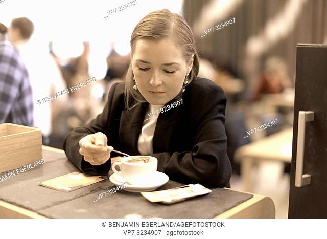 fashionable blogger woman trying coffee with little spoon, taking a break in café, in Munich, Germany