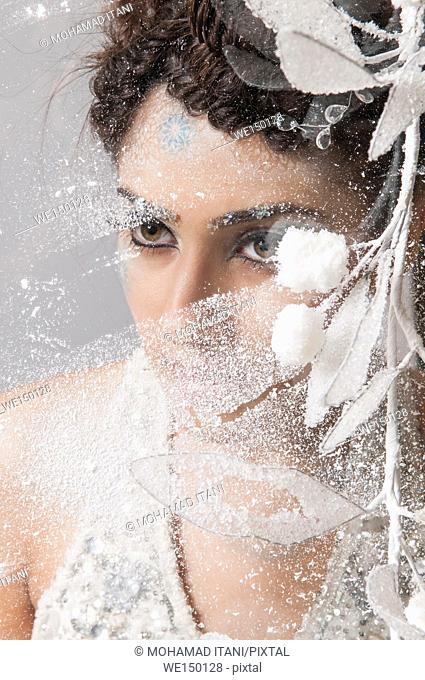 Serious woman looking through a frosted window