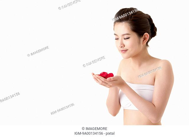 Young woman holding rose petals with eyes closed