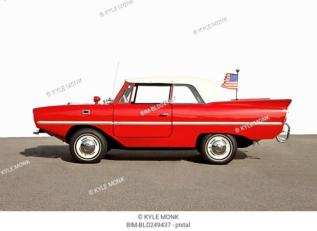 Red vintage convertible car with American flag