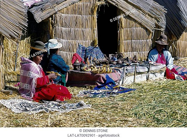 Women seated outside thatched reed house. Traditional clothes,hat. Selling,making traditional items,craft