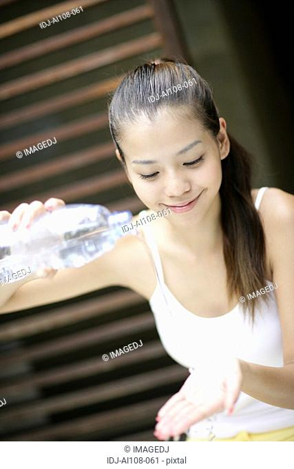View of a young woman pouring water on hands